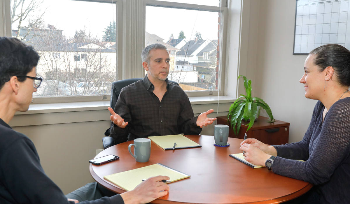 Photo of divorce guide talking with clients about the benefits of mediation.